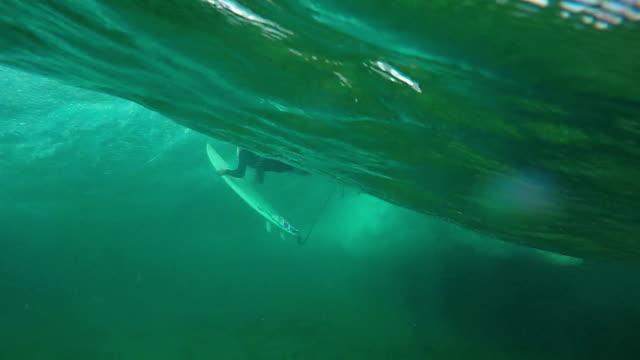 rallentatore sott'acqua: giovane professionista ragazza surfista facendo tuffo dell'anatra - sotto video stock e b–roll