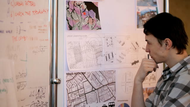 Young professional at urban development considers future areas given for construction, standing next to map and plans of area video
