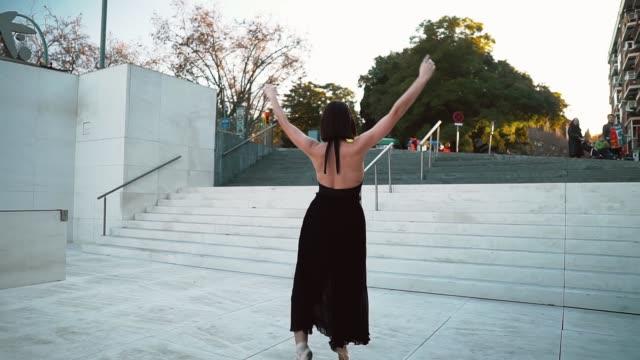 黒いドレスを着た若いプロのバレリーナは屋外で踊っています - チュチュ点の映像素材/bロール