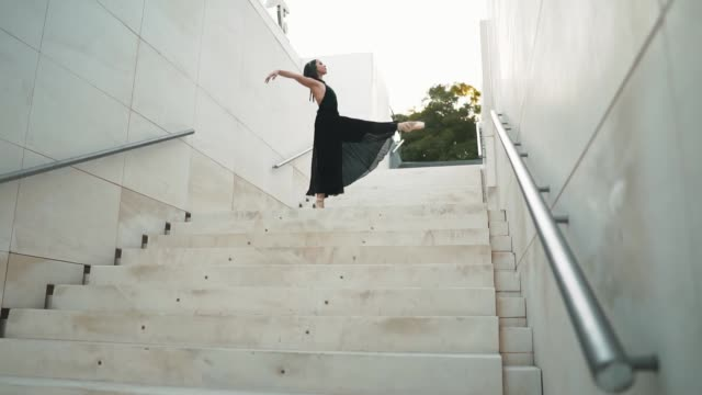 young professional ballerina in black dress is dancing outdoors young professional ballerina in black dress is dancing outdoors. ballet dancer is spinning and jumping high in a tutu and pointe shoes. . slow motion tutu stock videos & royalty-free footage