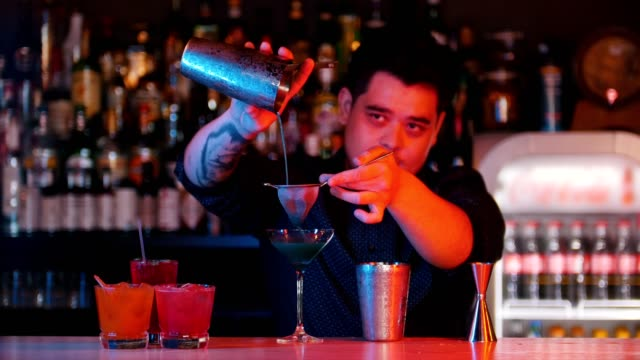 Young professional bartender pours blue liquor into a glass using a sieve