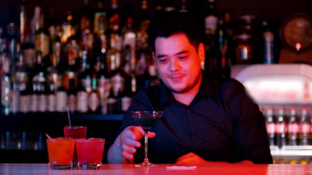 Young professional bartender puts a glass with a blue cocktail on a napkin and gives it forward