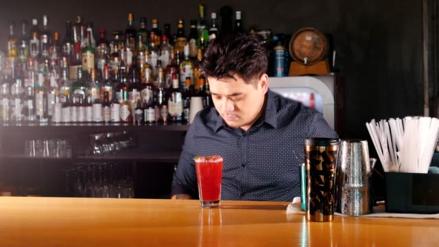 Young professional bartender puts the mint in prepared cocktail and pushed forward with a smile