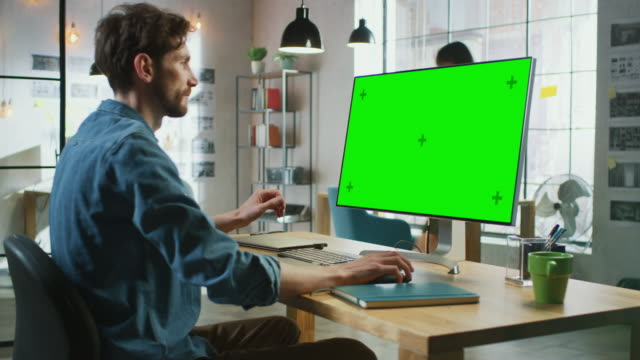 Young Professional Creative Employee Sits Down and Works on His Personal Computer with Big Green Screen Mock Up Display. He Works in a Cool Office Loft. Other Female Colleague Walks in the Background.