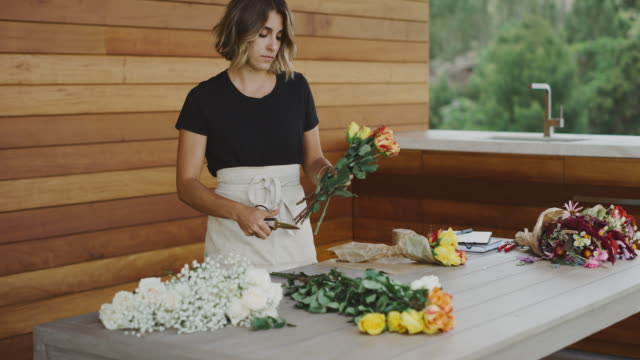 Young professional florist woman cutting flowers Young florist woman cutting flower stems preparing flowers for bouquets bunch stock videos & royalty-free footage