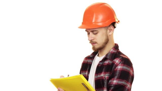 young professional male contractor in hardhat making notes smiling - craftsman architecture stock videos & royalty-free footage