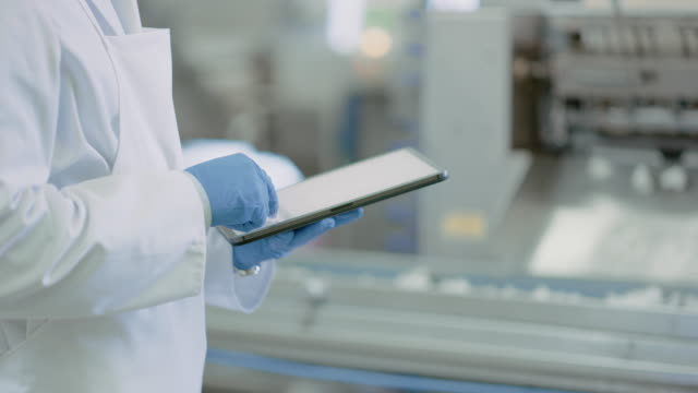 Video Young Quality Supervisor or Food Technician is Inspecting the Automated Production at a Food Factory. CLose Up Shot of an Employee Using a Tablet Computer for Work. He Types In Data While Wearing Latex Gloves.