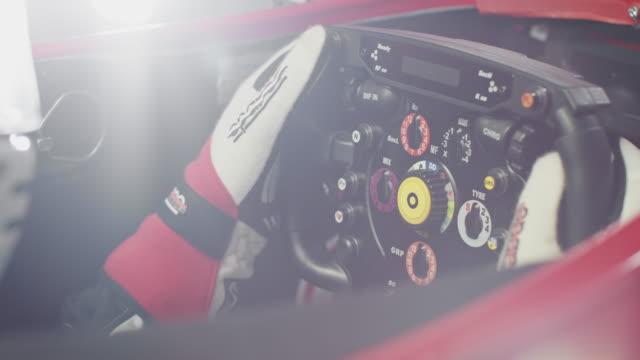 Young racer operating steering wheel in racecar