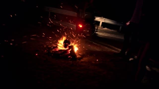 vidéos et rushes de young rebel amis motard debout autour de feu de camp dans la nuit - moto sport