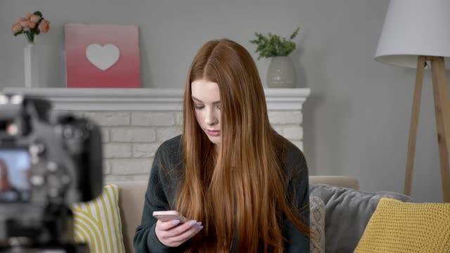 junge rothaarige mädchen blogger in die kamera, mit einem smartphone, sms, tippen, nach hause gemütlichkeit im hintergrund. 60fps - kosmetik beratung stock-videos und b-roll-filmmaterial