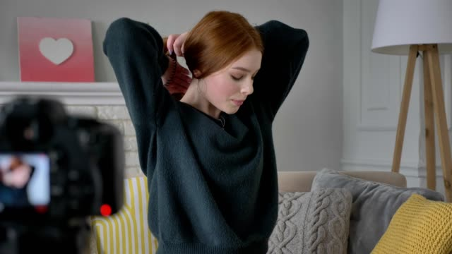 Young red-haired girl blogger, smiling, talking at the camera, Makes herself a hairstyle, tress, home comfort in the background. 60 fps video