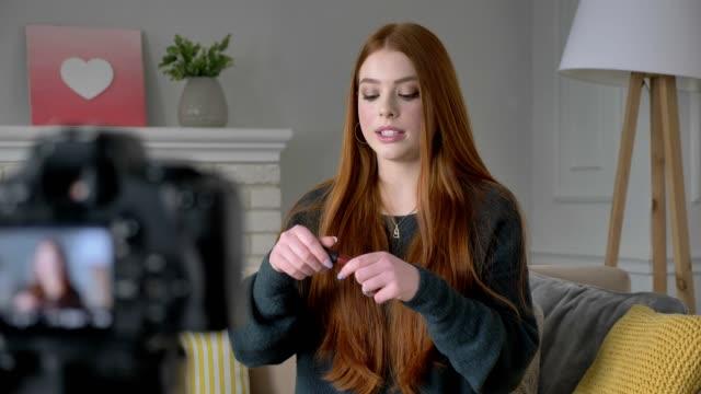 junge rothaarige mädchen blogger, lächelnd in die kamera sprechen, zeigt eine neue kaufen, kosmetik, lipgloss, make-up-konzept, wohnkomfort im hintergrund. 60fps - kosmetik beratung stock-videos und b-roll-filmmaterial