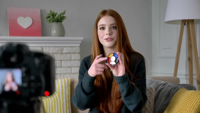Young red-haired girl blogger, smiling, talking at the camera, showing a new purchase, cosmetics, Eyeshadow Pallet, home comfort in the background. 60 fps video