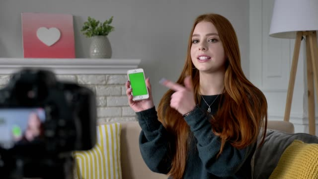 Young red-haired girl blogger, smiling, talking at the camera, showing a new purchase, smartphone, application, green screen, chroma key, home comfort in the background. 60 fps video