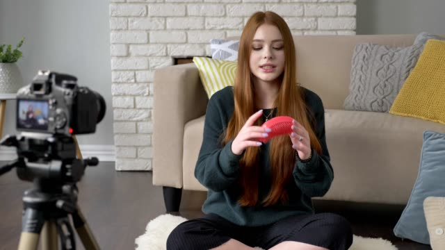 Young red-haired girl blogger, smiling, talking at the camera, showing a new purchase, red comb, make-up concept, home comfort in the background. 60 fps video