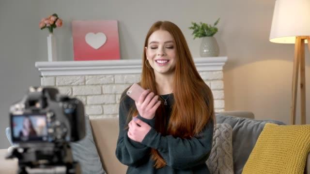 junge rothaarige mädchen blogger, lächeln, sprechen vor der kamera, mit smartphone-gesten mit den händen, wohnkomfort im hintergrund. 60fps - kosmetik beratung stock-videos und b-roll-filmmaterial