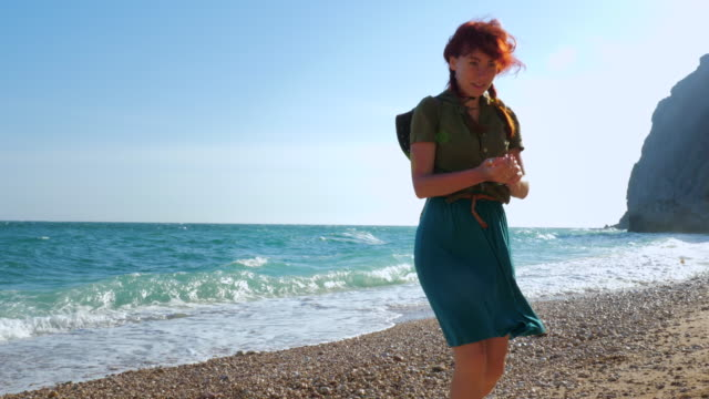 Young red-haired girl traveler with a cowboy hat and a backpack wanders along the sea beach. Young red-haired girl traveler with a cowboy hat and backpack walks on the sea beach, smiling and enjoying life. pigtails stock videos & royalty-free footage