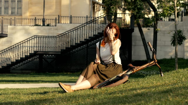 young redhaired woman cyclist lying on green grass at city park in summer day - ragazza auricolari rossi video stock e b–roll