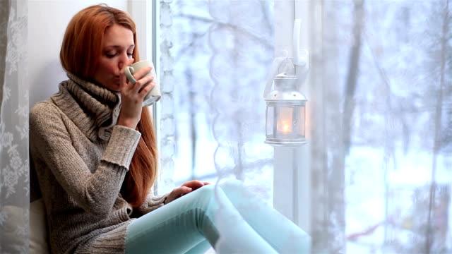 giovane donna a pelo rossa seduto sulla windowsill, guardando la finestra e beve tè. fuori la finestra invernale. - davanzale video stock e b–roll