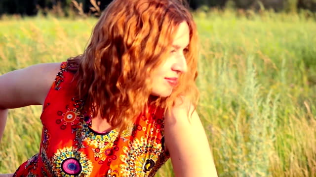 young red-haired woman with full red lips posing to photographer at summer outdoor on nature