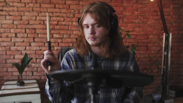 vídeos de stock e filmes b-roll de young redhead man drummer in headphones playing electric drums at home, slow motion, dolly shot - bateria instrumento de percussão