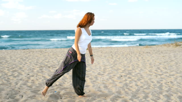 Young redhead woman at early 30s meditating on the beach IV video