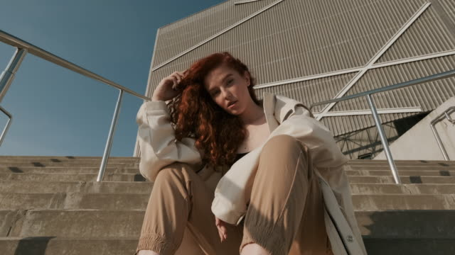 Young Redheaded Girl. Urban Fashion Concept. Young Red-Haired Girl On The Street. Girl Has Long Curly Hair. Urban Fashion Concept. urban fashion stock videos & royalty-free footage