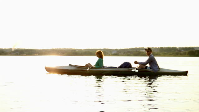 Young relaxed couple having rest on boat after rowing exercise video