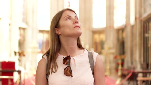 Young religious woman tourist walking in catholic church. European cathedral: inside of holy place video