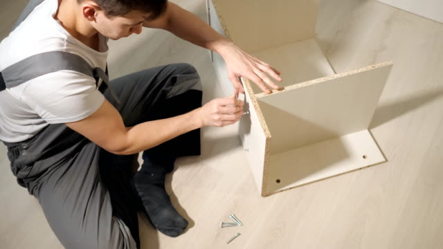 Young repairman assembling new table at home interior Young repairman assembling new table at home interior. cabinet stock videos & royalty-free footage