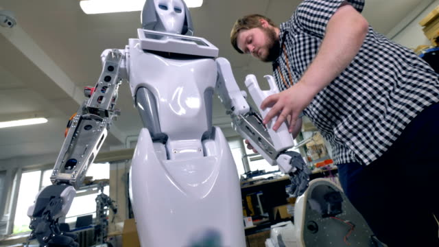 A young repairman covers robots steel frame on forearms. video