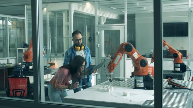 vídeos de stock, filmes e b-roll de jovens pesquisadores estão olhando para máquinas robóticas em movimento - engenheiro
