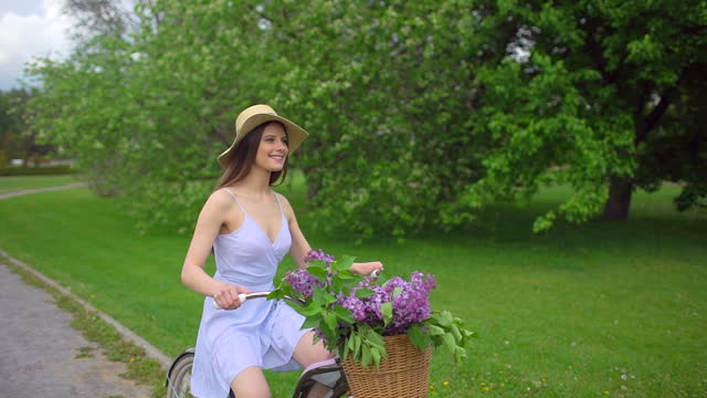 Young romantic beautiful traveler girl with hat and dress with retro vintage bicycle in sunset forest