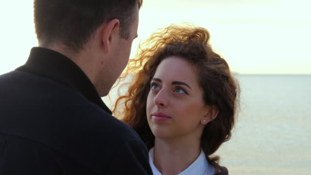 Young romantic couple in trendy wear on date, enjoying moment of closeness on sea or ocean background. Woman with curly hair smiling to her man. Romantic concept. 4k video