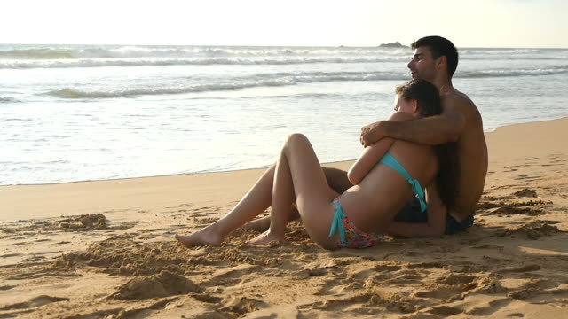 Young romantic couple is enjoying beautiful view sitting on the beach and hugging. A woman and a man sits together in the sand on the seashore, admiring the ocean and landscapes.Slow motion Close Up video