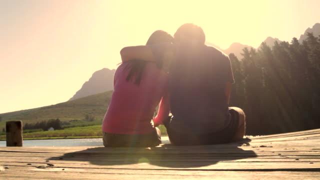 Joven Pareja romántica sentado en el embarcadero con vista al lago - vídeo
