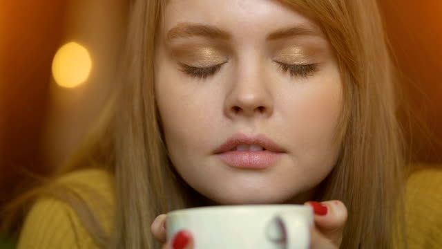 Young romantic women drinking coffee in city cafe