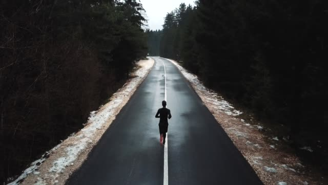 young runner running on the road to mountain, drone shot of a runner from above.young athlete on quiet autumn deserted pass. cinematic drone back view - koncentracja filmów i materiałów b-roll