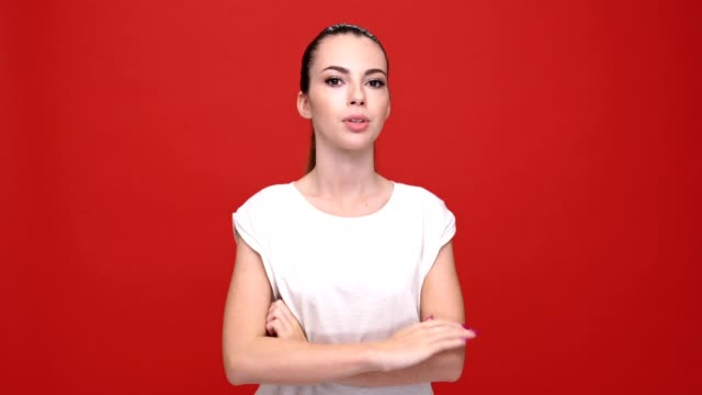Young sad pretty caucasian woman thinking over red background. video