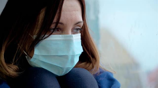 Ung ledsen kvinna i medicinsk mask sitter på fönstret och tittar på hennes reflektion. Hälso- och sjukvård och medicinskt koncept video