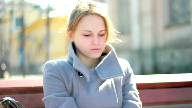Young sad woman sitting outdoors alone, feeling emotional stress video