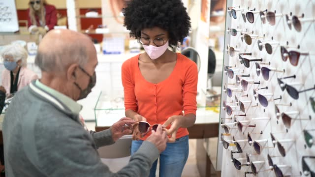 Young saleswoman assisting a senior customer buying eyeglasses in an optical store, both wearing face mask