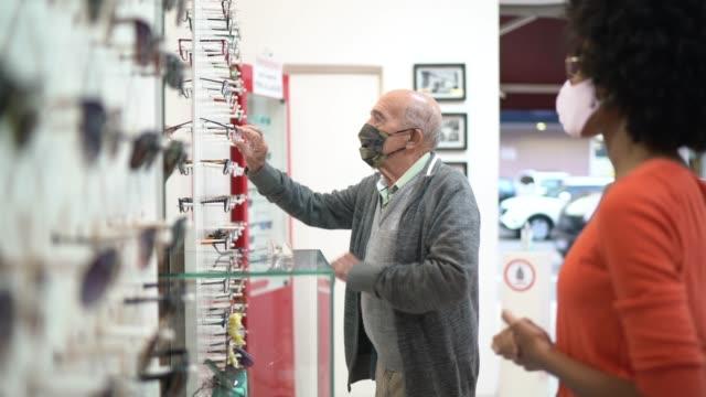 stockvideo's en b-roll-footage met jonge verkoopster die een hogere klant bijstaat die oogglazen in een optische opslag koopt, allebei dragend gezichtsmasker - lens optisch instrument
