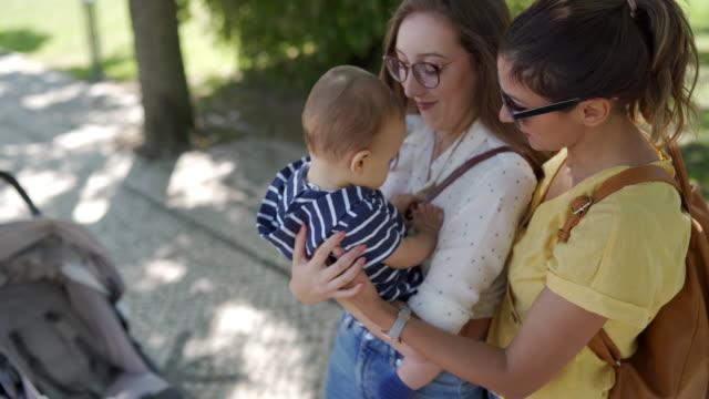 unga samma kön par adoringly leende på deras baby boy - femininitet bildbanksvideor och videomaterial från bakom kulisserna