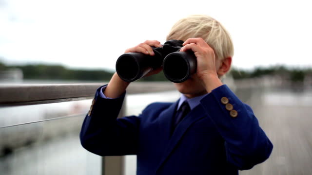 young school boy lookng through binoculars over a balustrade video