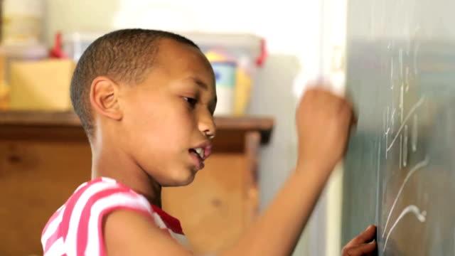 Young School Boy funciona un cálculo suma en una pizarra de tiza - vídeo