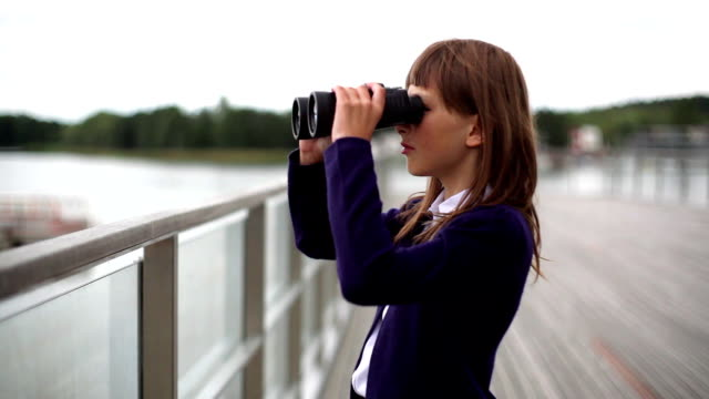 young school girl lookng through binoculars over a balustrade video