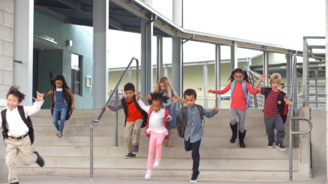 vídeos y material grabado en eventos de stock de jóvenes escuela niños de salto pasos que abandonan la escuela - despedida