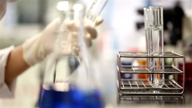 Young scientist in medical laboratory estimate chemicals in tube video