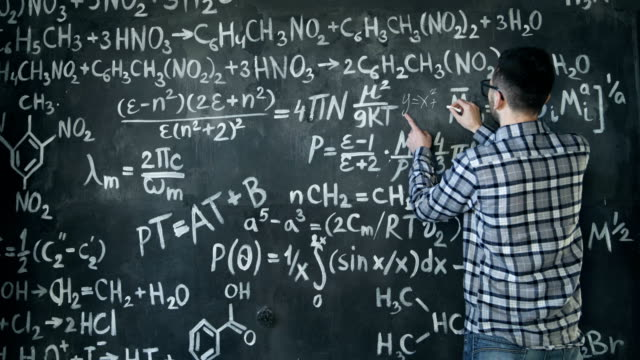 Young scientist man write chock in chemical and mathematical equations wall room interior video